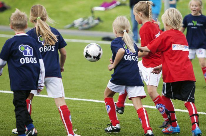 Barn fra to fotballag kjemper om ballen i fotballcup