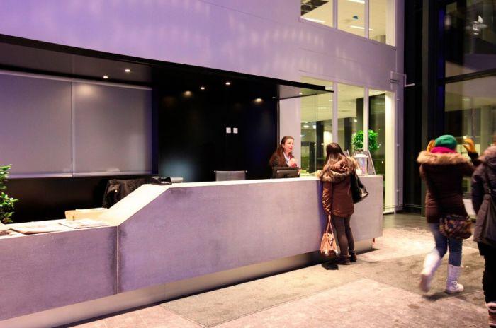 Bilde av resepsjonsområdet inne i Kværnerhallen. Betongflater opplyst i lys lilla og inngangsparti i mørkt stål og store glassflater.