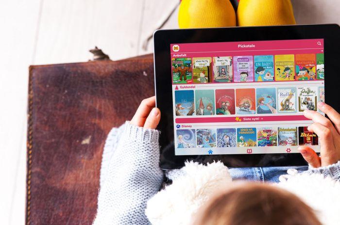 Barn som holder en iPad med Pickatale