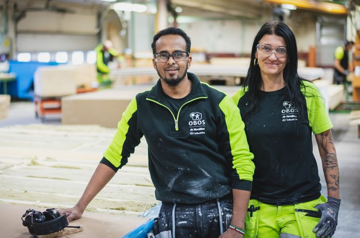 En kille och en tjej som arbetar på en obos fabrik