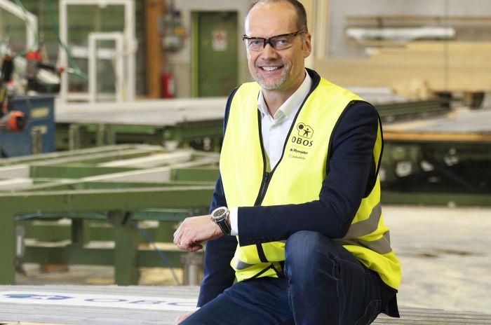 Joakim Henriksson, VD för OBOS Sverige sitter med skydddskläder i en fabrik
