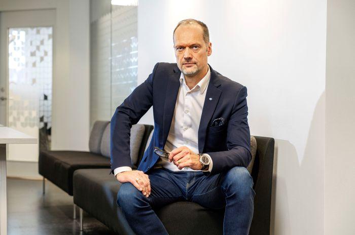 Joakim Henriksson, VD för OBOS Sverige, sitter på en soffa i ett kontorslandskap
