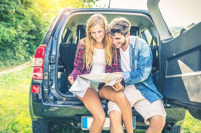 en tjej och en kille tittar på en karta i en avis hyrbil