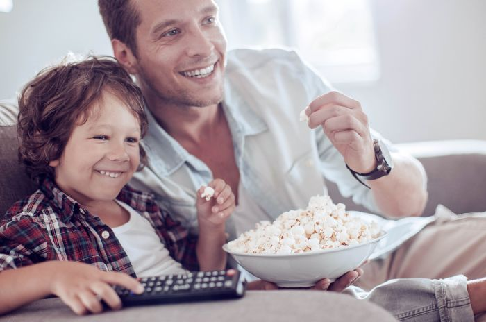 Pappa och son som äter popcorn samtidigt som de tittar på TV