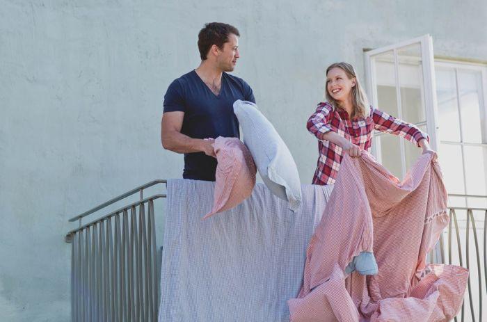 man och kvinna står och vädrar täcke och kudde på balkong