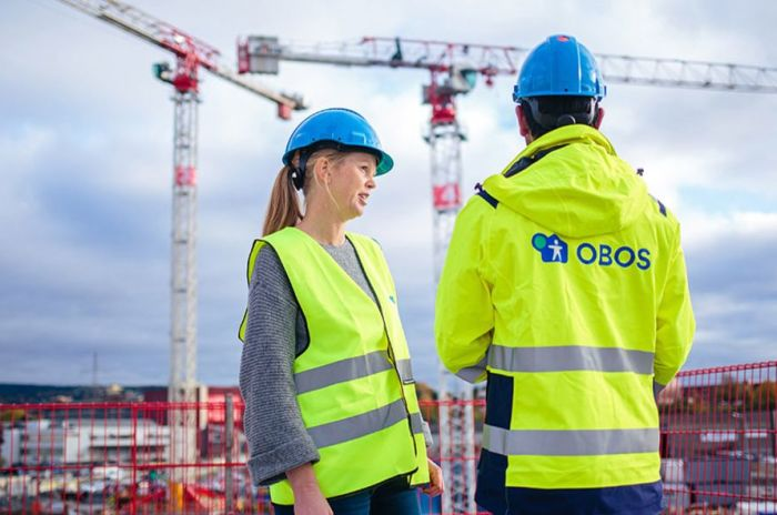 En tjej och en kille står i OBOS skyddskläder på en byggarbetsplats
