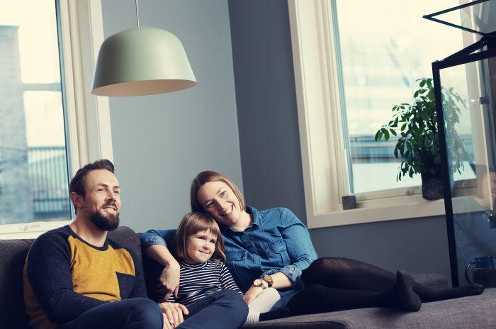 Familie sitter sammen i sofaen og ser samlet på noe på TV