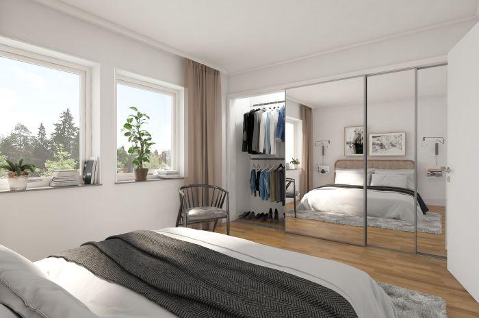 En dubbelsäng och en spegelvägg i ett sovrum