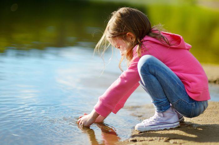 Flicka sitter vid vattenrbynet vid sjö
