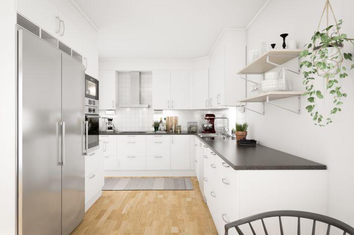 Kök i öppen planlösning med ljusa färger och kyl och frys i rostfritt stål