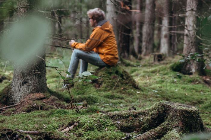 En man som sitter på en stubbe i en skog