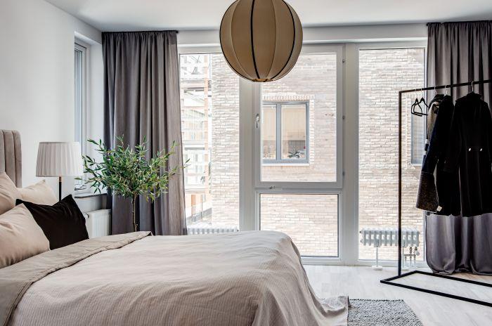 En bäddad säng med ljusa lakan och en beige lampa i taket