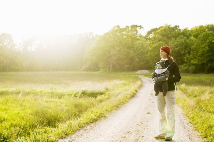En kvinna och ett barn på en grönskande landsväg