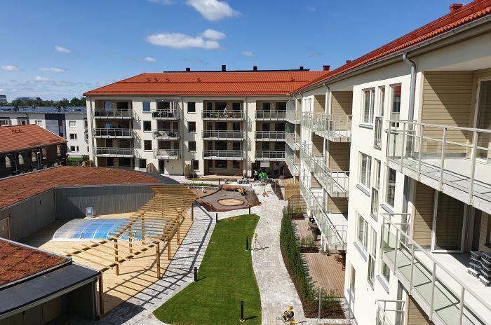 Ett hus med flera lägenheter och en pool på innergården
