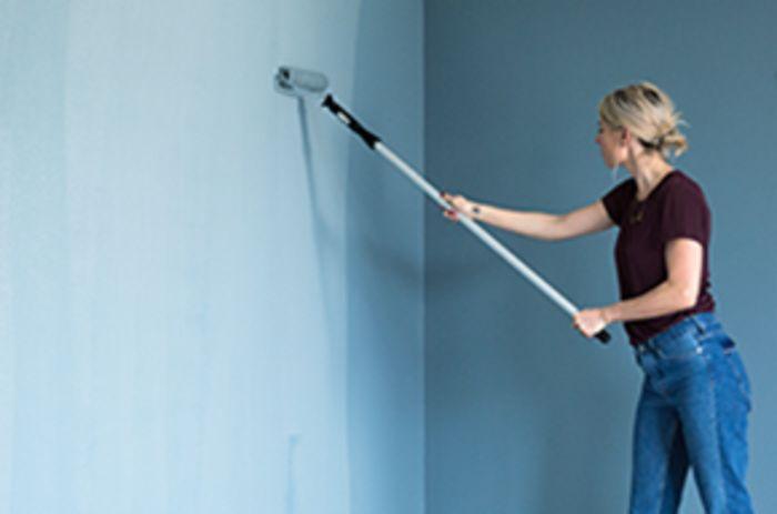 Kvinna som målar en vägg