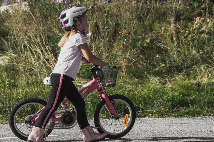 En flicka som leder sin cykel