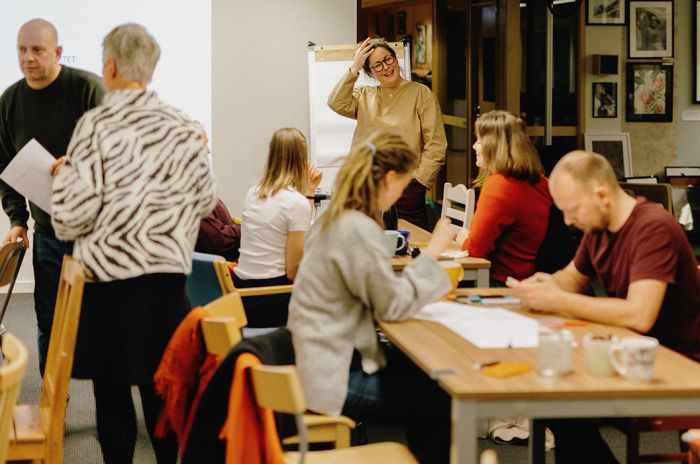 Foto viser deltakere på medvirkningsmøtet om Living Lab som jobber med oppgaver.