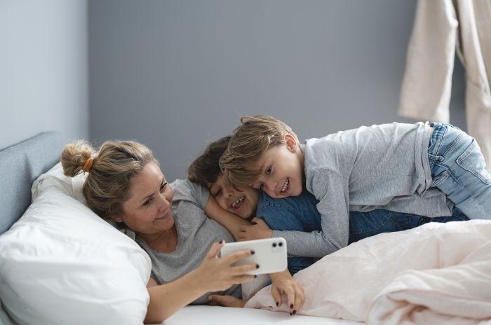 Glad kvinna med barnen på en säng kollar in OBOS-appen på mobilen