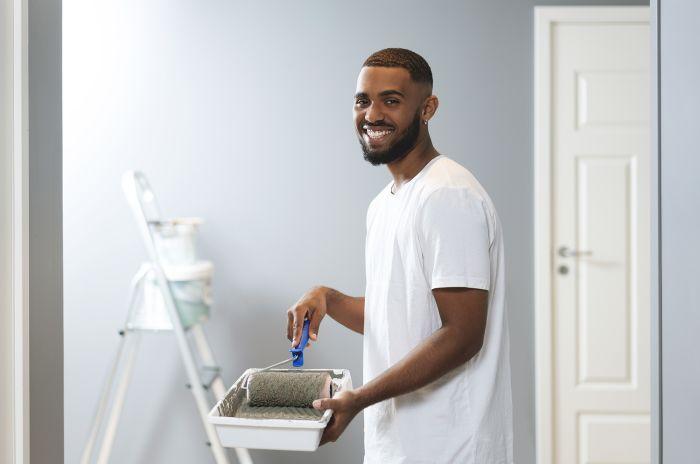Ung man målar rum i OBOS-hem