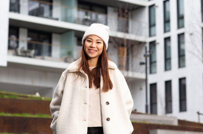 Ung kvinne smiler til kamera foran boligblokker i Barcode