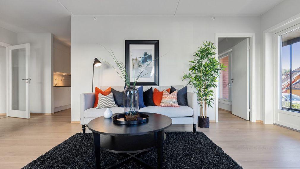 Bilde av stue med sofa og bord, inngang til kjøkken og soverom i Industrigata 20