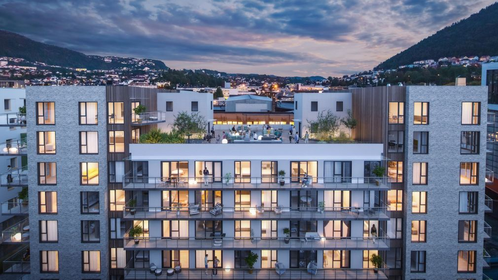 Kveldsbilde av boligblokk i Kronstadparken med private terrasser og felles takterrasse