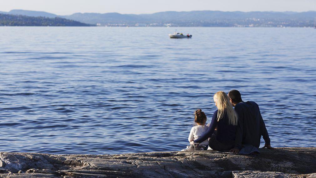familie sitter på svaberg og ser ut over sjøen