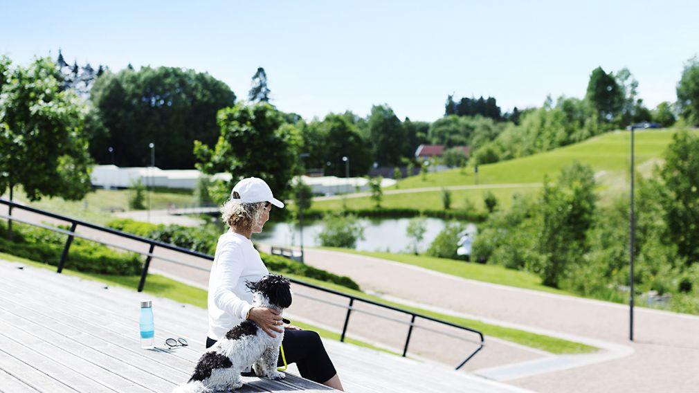 Bilde av kvinne og hund som sitter og hviler seg i grøntområder