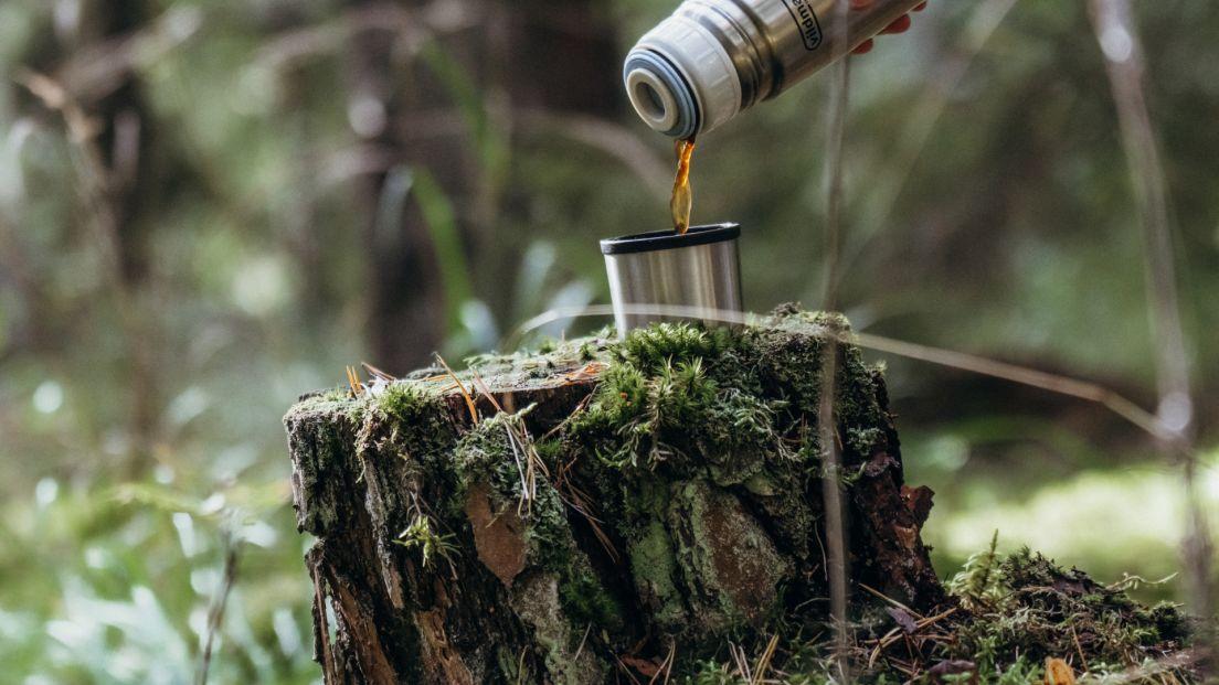 Kaffe hälls upp från en termos på en stubbe i Skölsta