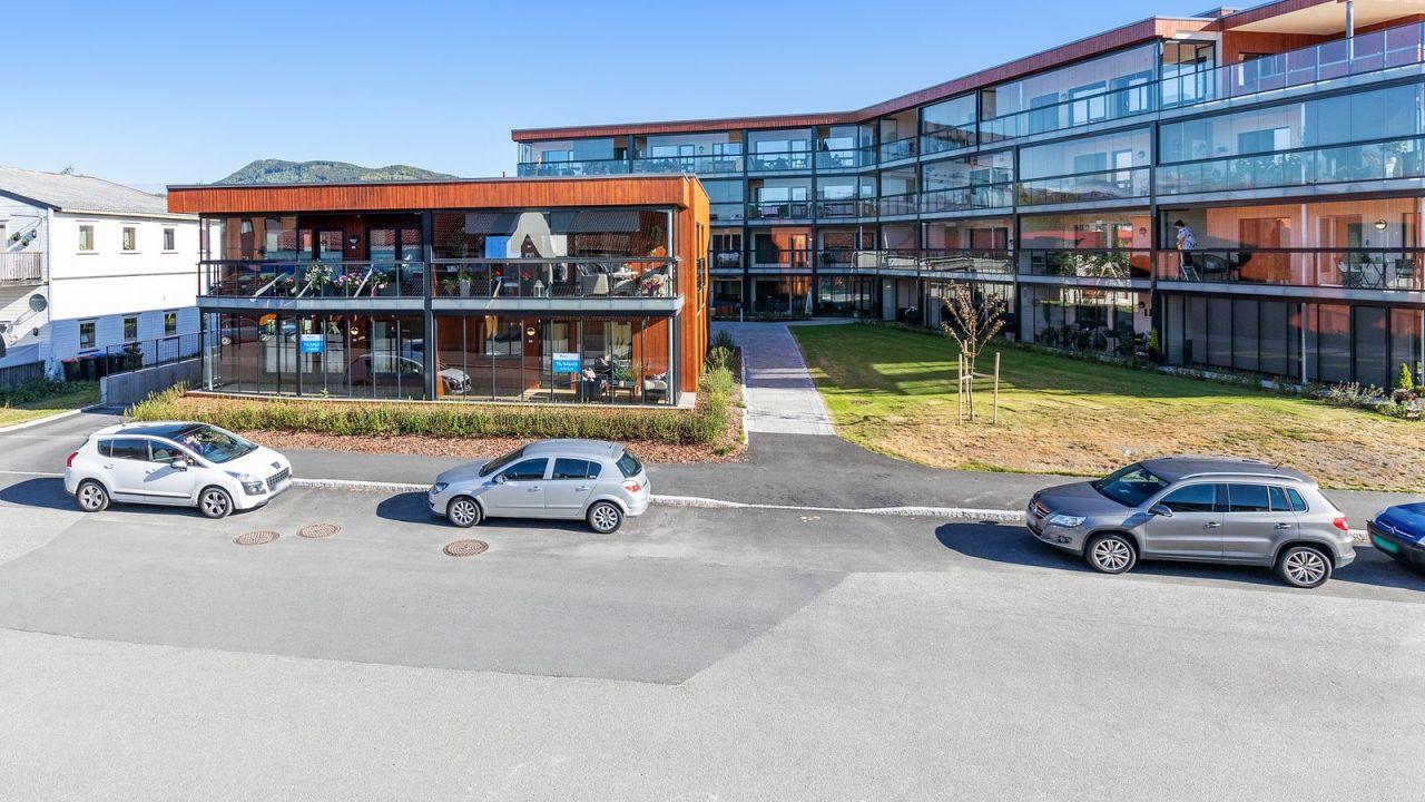 Bilde av fasade på Industrigaten med gressplen og parkerte biler i veien