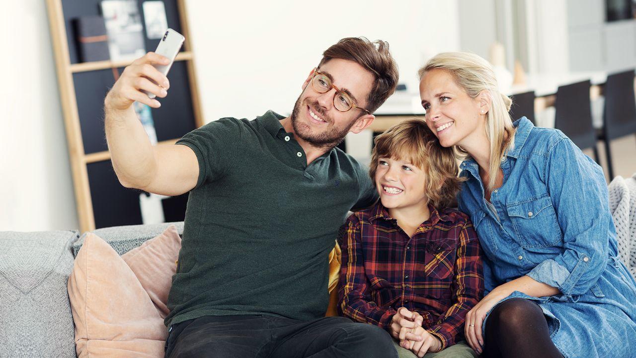 Familie som tar selfie i sofaen