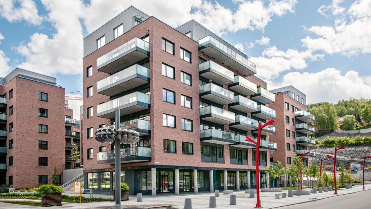 Bilde av Smeltedigelen 4. Moderne leilighetsbygg i 5 etasjer. Forretninger i første etasjer. Store glassflater, balkonger og rød murstein.