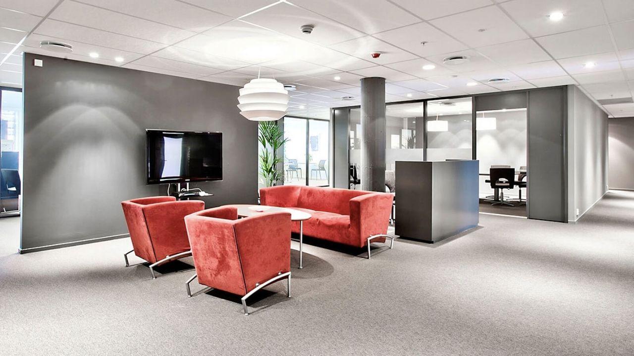 Bilde av Ulvenveien 111. Moderne kontorlandskap i gråtoner og rød sittegruppe og hvit designlampe. Lysegrått teppe på gulvet og grå fontvegg. Innslag av grønne planter.