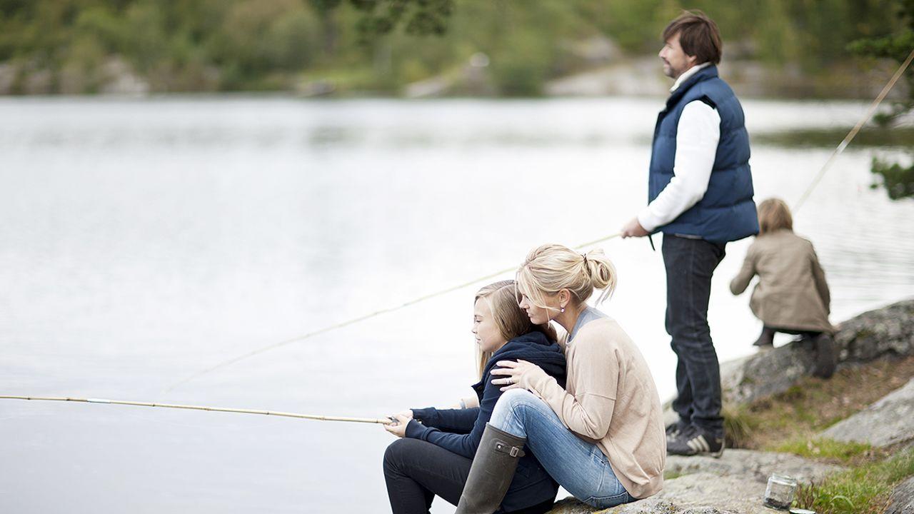 Bilde av familie står og fisker ved vannet med fiskestenger