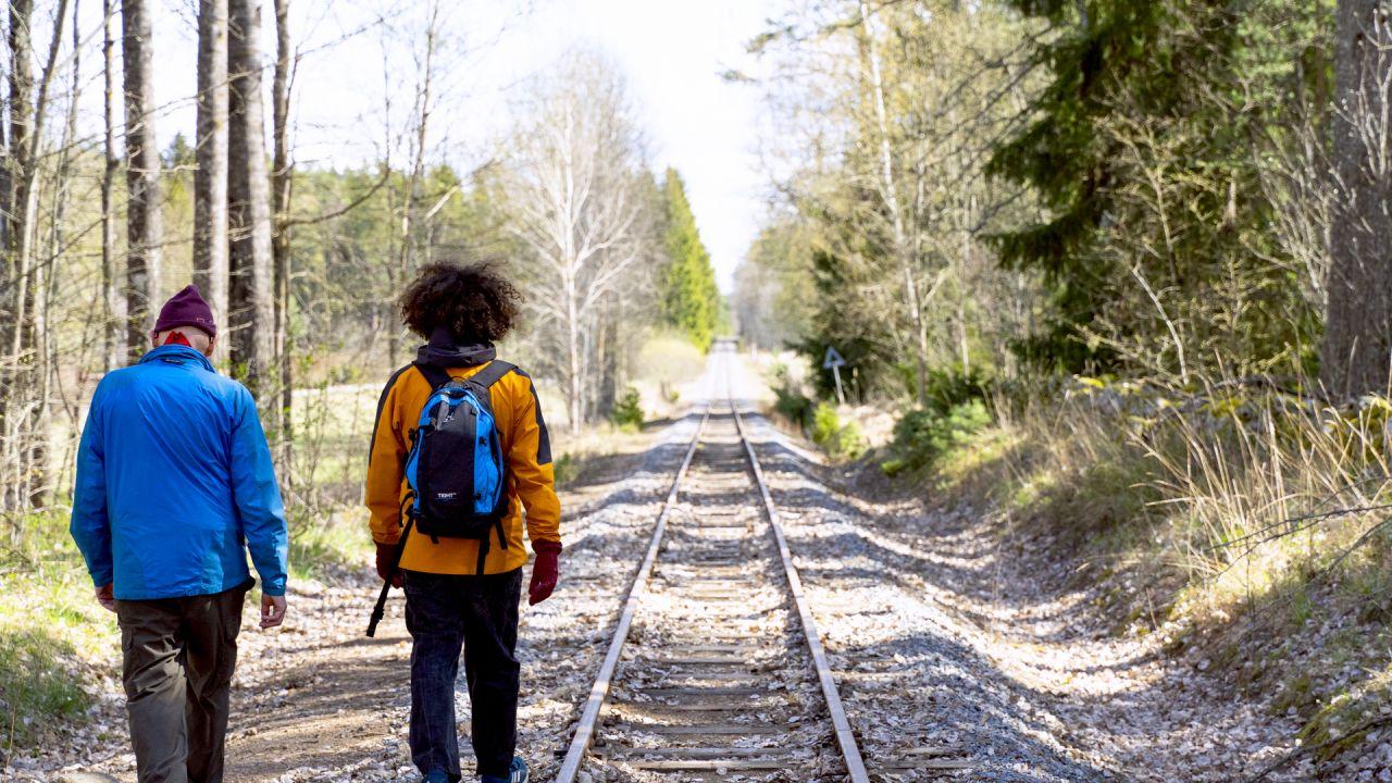 En man och en kvinna som går längst ett järnvägsspår