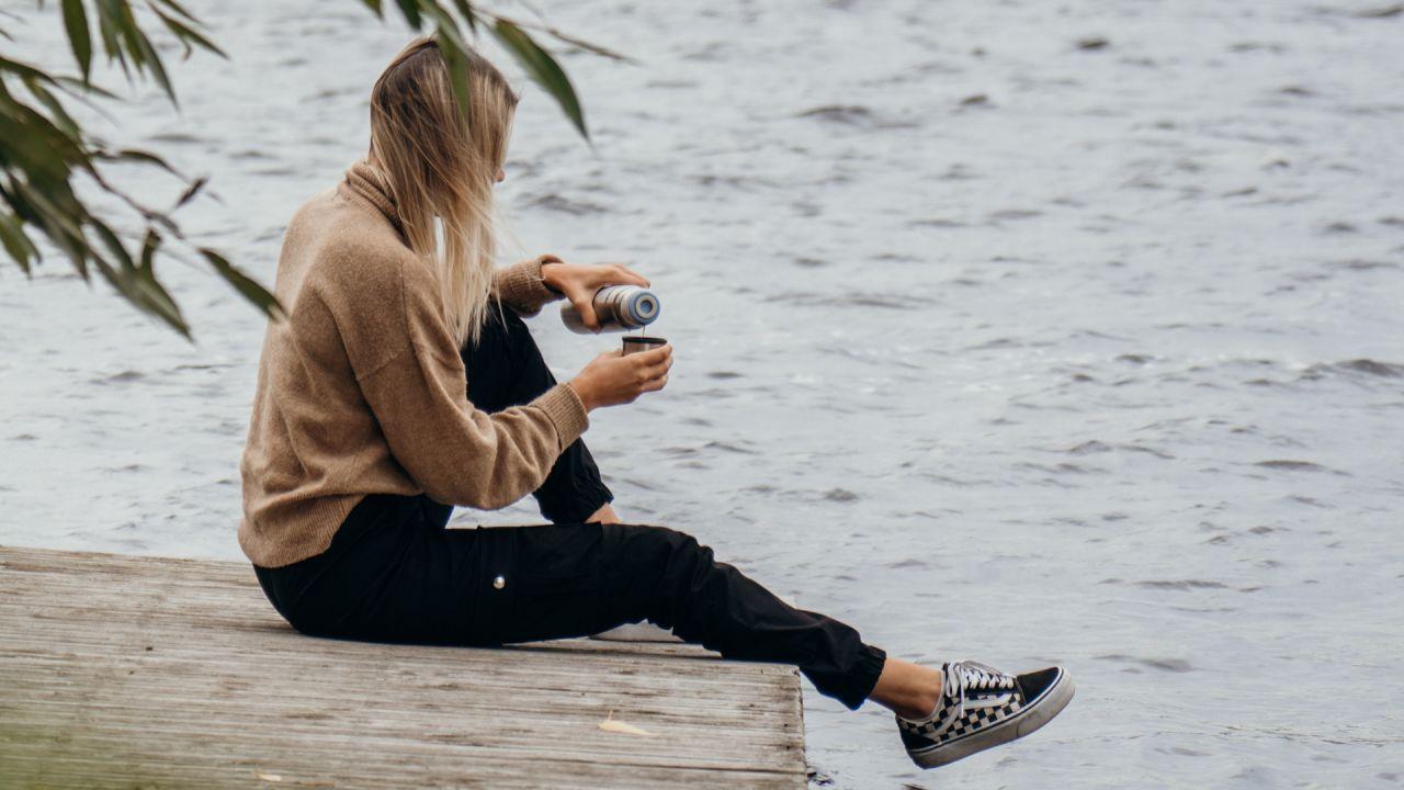 kvinna sitter och häller upp kaffe ur termos på brygga