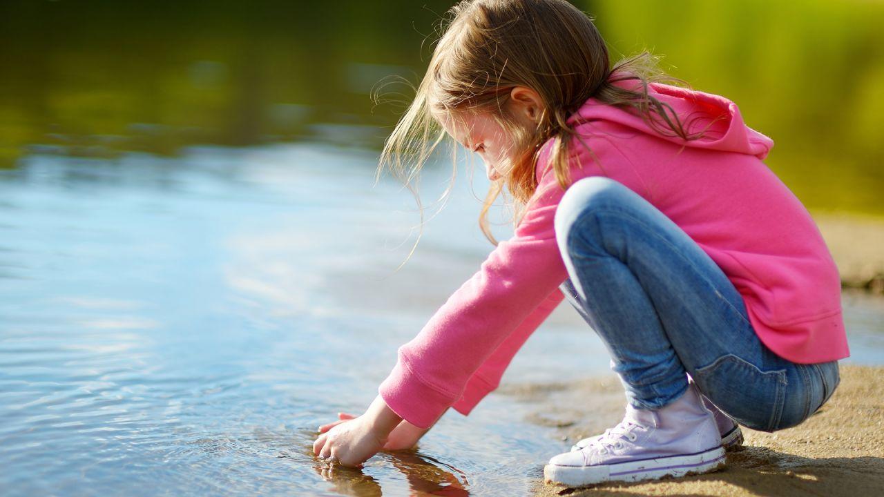 flicka sitter i vattenbrynet vid stranden