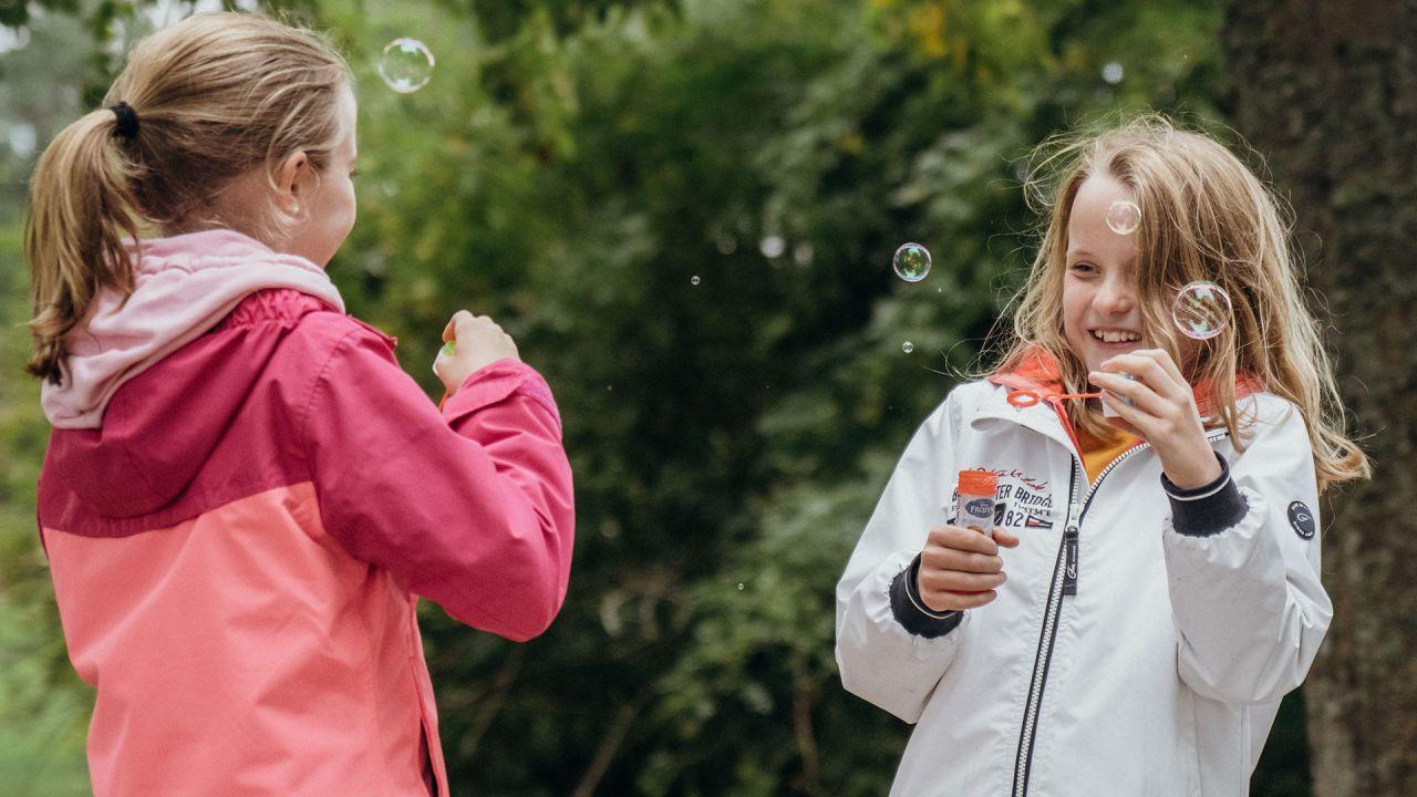 Två flickor som blåser såpbublor i en grön miljö