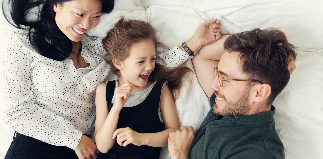 En familj med ett barn tittar på varandra i en säng