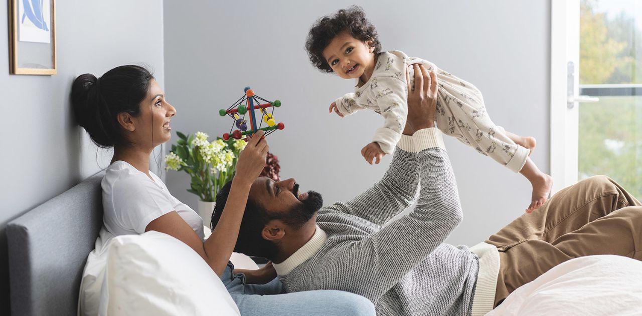 En familie i en seng. Far holder barn oppe i lufta.