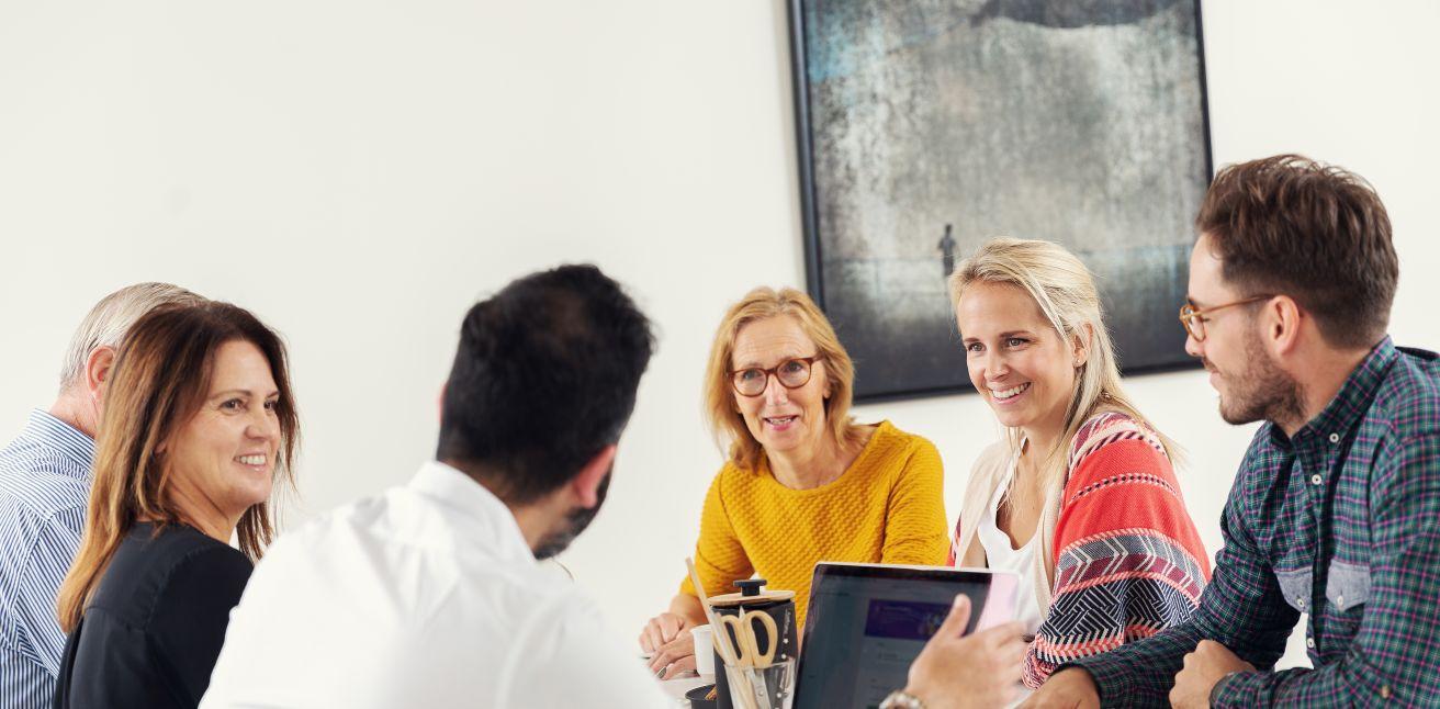 Bilde av seks smilende mennesker rundt et møtebord