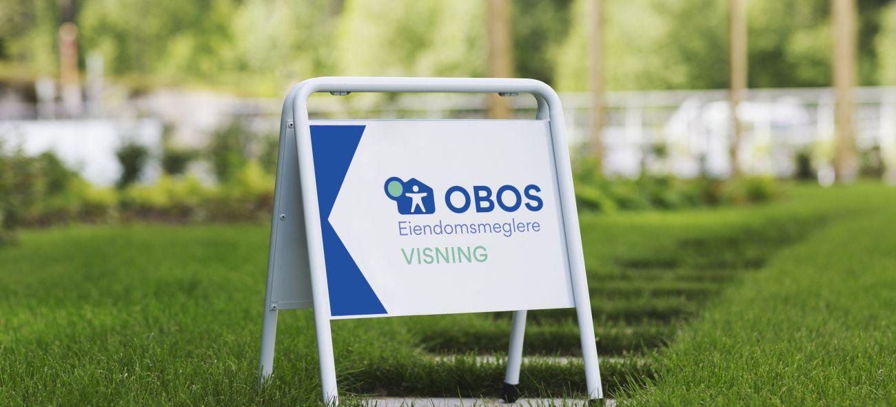 OBOS Eiendomsmeglere-skilt på en gressplen