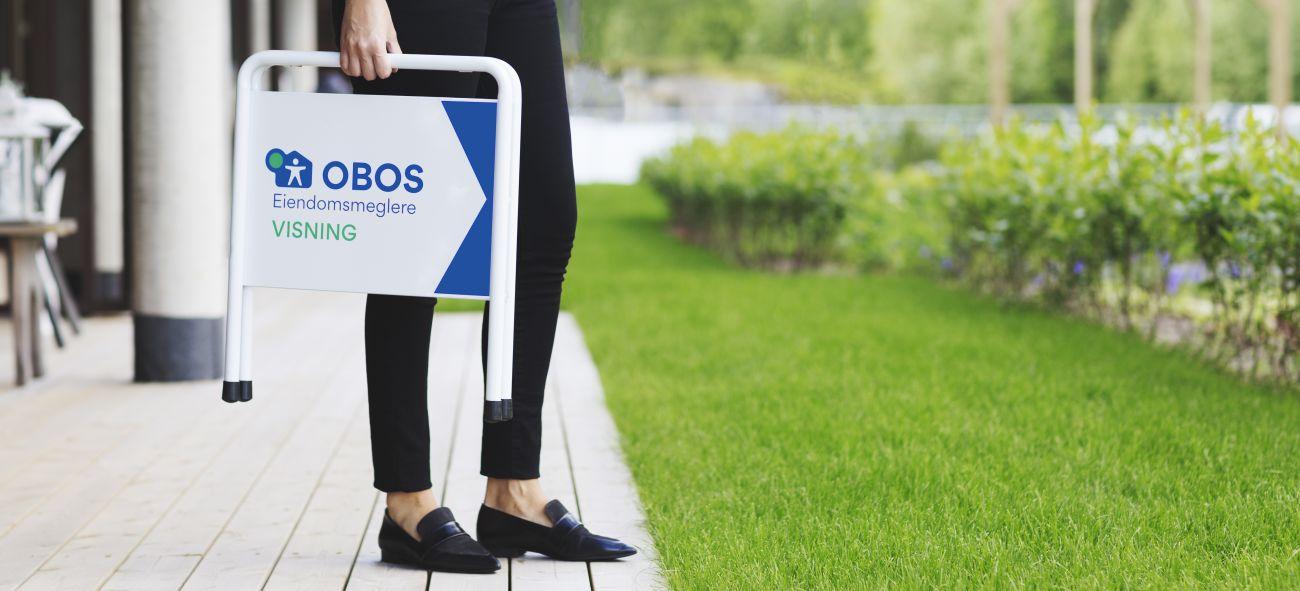 En megler står med et OBOS EIendomsmeglere-skilt