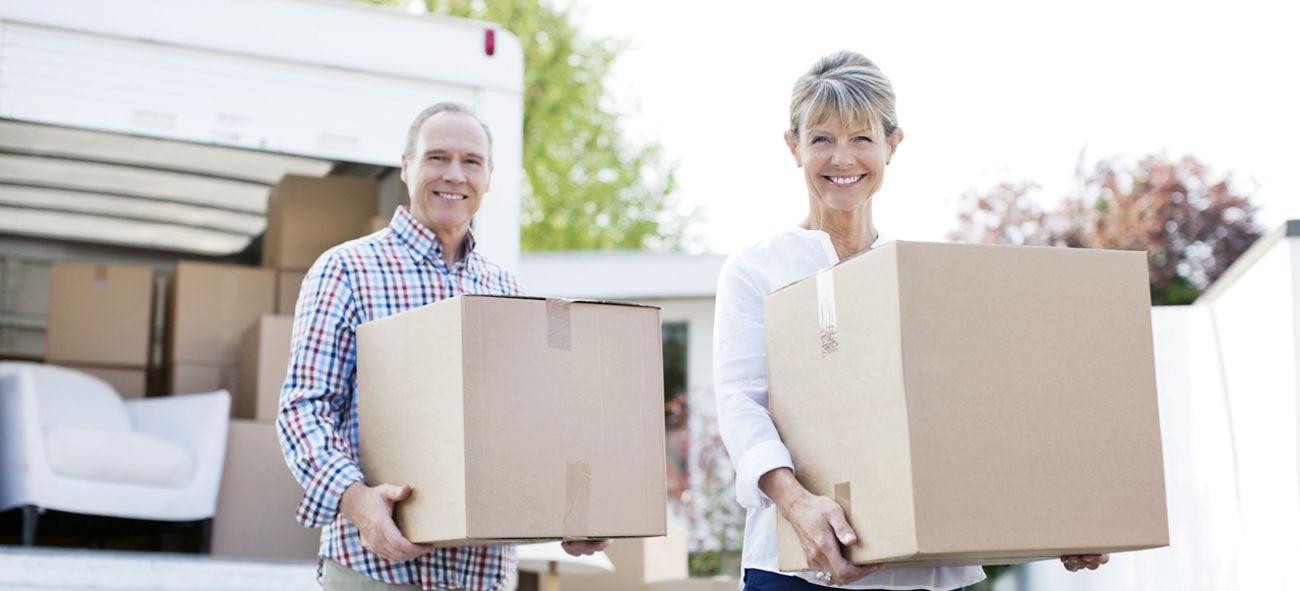 eldre par står med flyttekasser i hendene