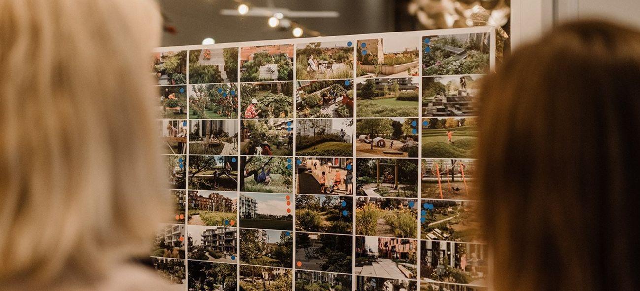 Bilde viser to kvinner som ser på en vegg med masse små bilder av Fornebu.