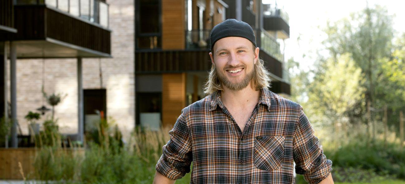 Mann med caps og rutete skjorte smiler foran boligblokk