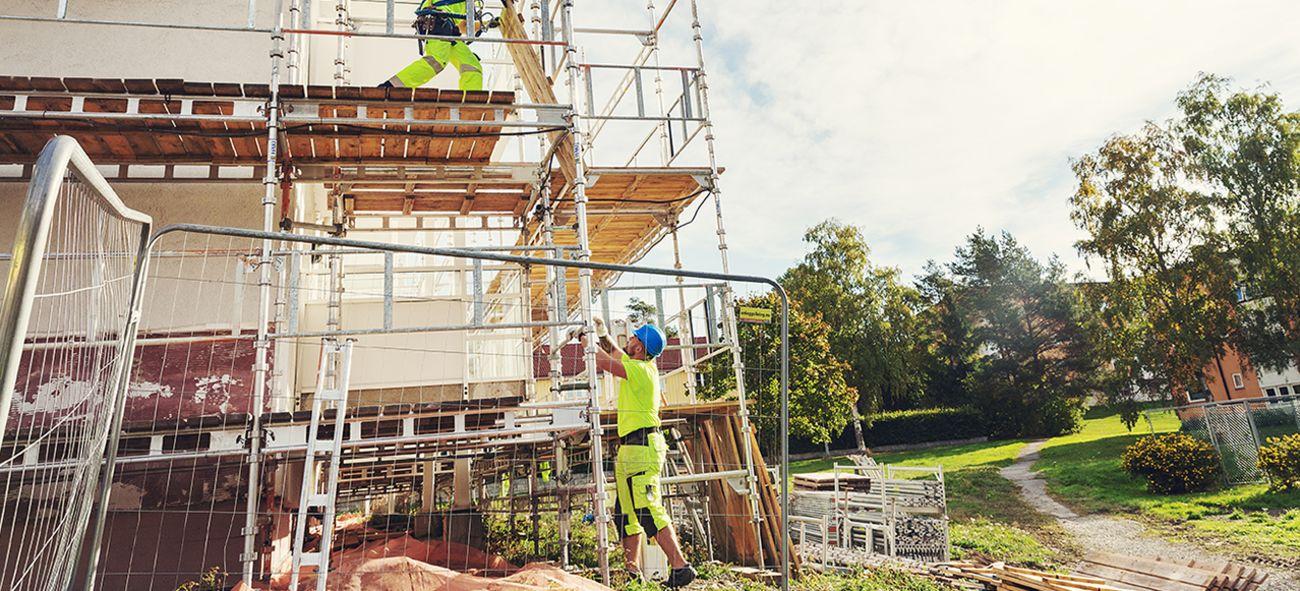To menn bygger stilaser i forbindelse med rehabilitering av fasaden på en boligblokk