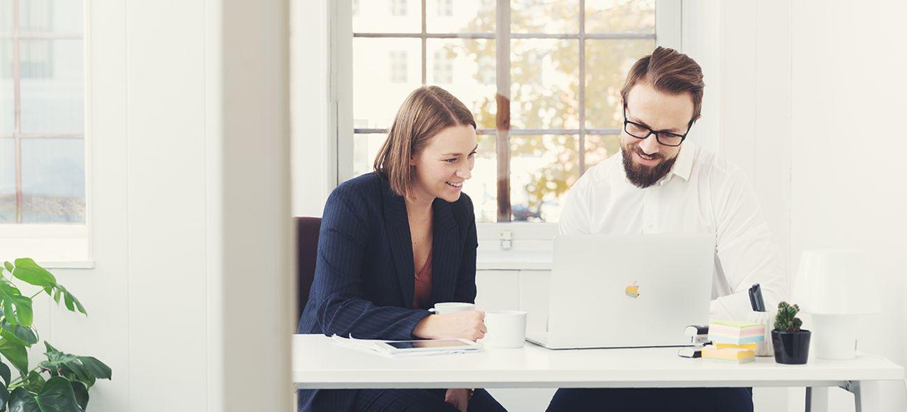 Dame og mann som sitter foran PC og arbeider