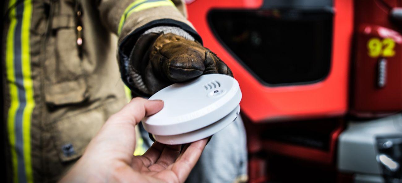 Hånda til en brannkonstabel som legger en røykvarsler i hånda på en person