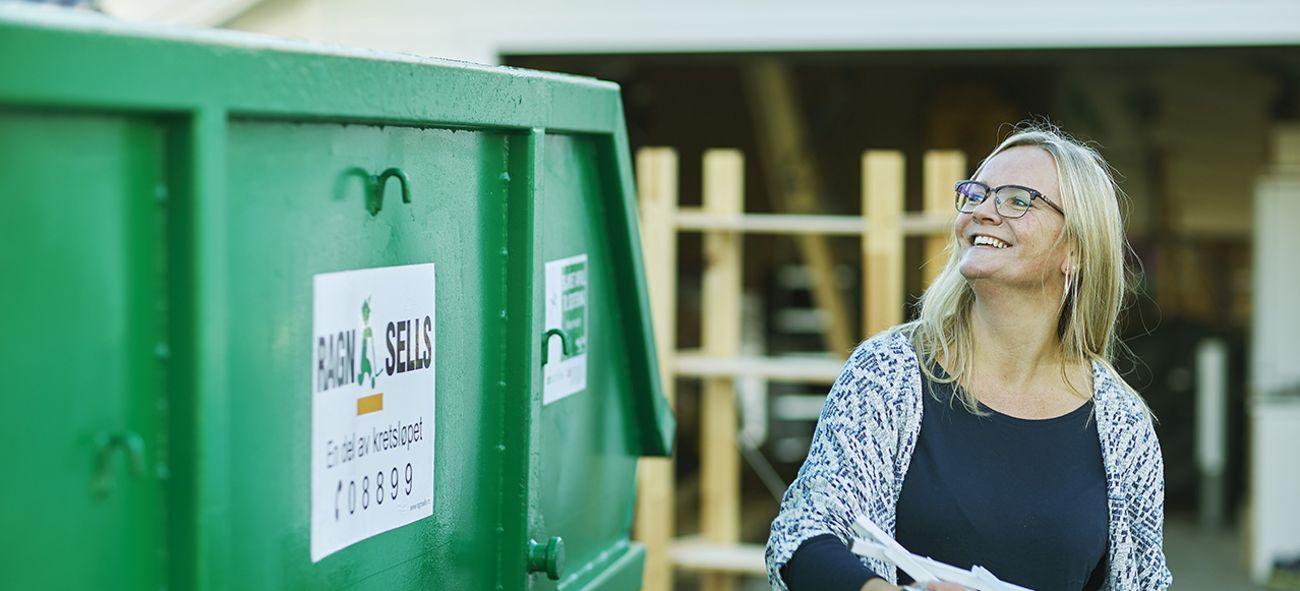 en dame kaster søppel i en container